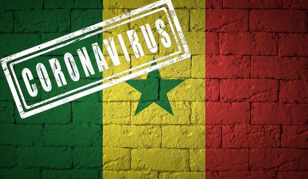 Flagge des senegals auf backsteinmauerbeschaffenheit. gestempelt mit coronavirus. konzept des corona-virus. am rande einer covid-19- oder 2019-ncov-pandemie. neuartiger chinesischer coronavirus-ausbruch