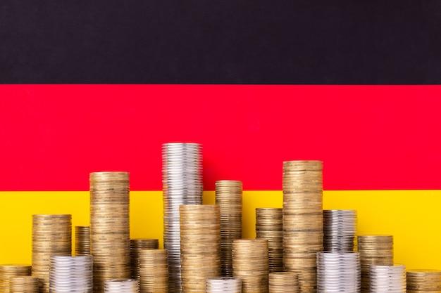 Flagge deutschlands mit stapeln von gold- und silbermünzen