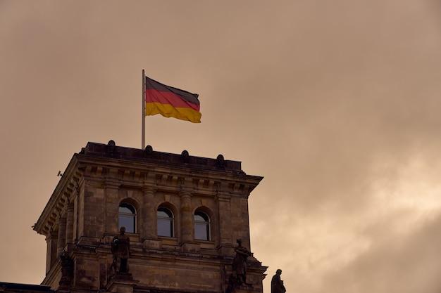 Flagge deutschlands vor dem hintergrund eines bewölkten himmels.