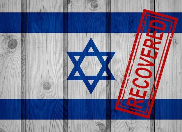 Flagge israels, die die infektionen der corona-virus-epidemie oder des coronavirus überlebt oder sich davon erholt hat. grunge-flagge mit stempel wiederhergestellt