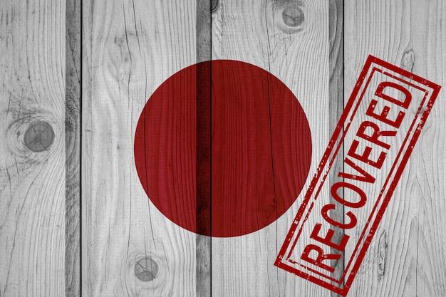 Flagge japans, die die infektionen der corona-virus-epidemie oder des coronavirus überlebt oder sich davon erholt hat. grunge-flagge mit stempel wiederhergestellt