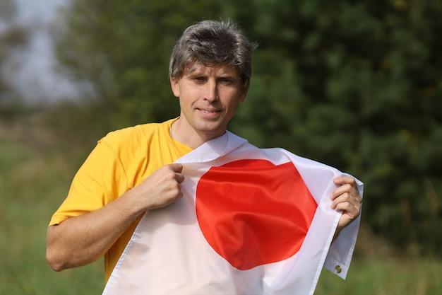 Flagge japans in den händen eines mannes kaukasischer rasse