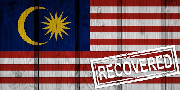 Flagge malaysias, die die infektionen der corona-virus-epidemie oder des coronavirus überlebt oder sich erholt hat. grunge-flagge mit stempel wiederhergestellt