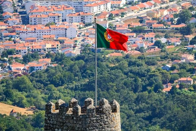 Flagge portugals auf der burg von sintra mit blick auf die stadt lissabon.