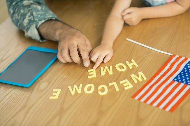 Flagge und tablet. nahaufnahme von militäroffizier und tochter, die mit flagge und tablet am tisch sitzen