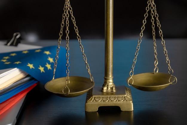 Flagge und waage der europäischen union am arbeitsplatz des anwalts oder im büro.