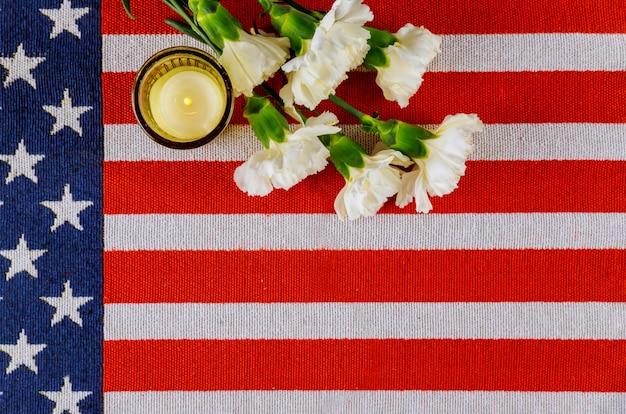 Flagge von amerika mit weißen nelkenblumen und brennender kerze