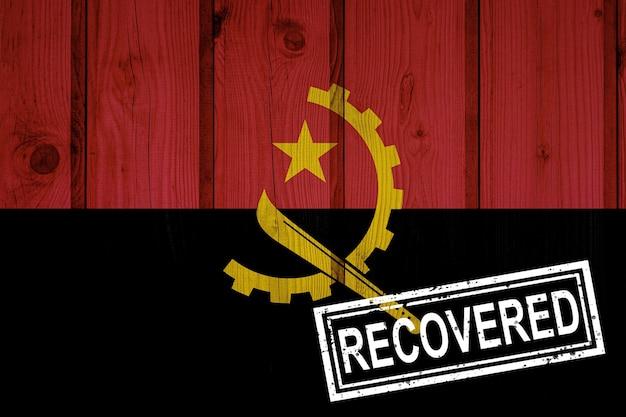 Flagge von angola, die die infektionen der corona-virus-epidemie oder des coronavirus überlebt oder sich davon erholt hat. grunge-flagge mit stempel wiederhergestellt