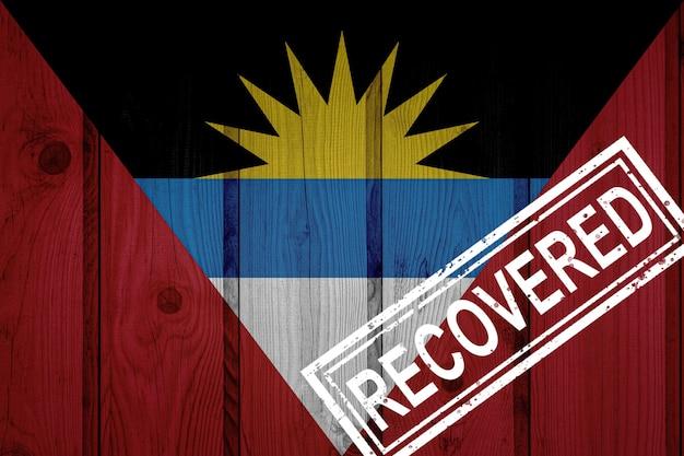Flagge von antigua und barbuda, die die infektionen der corona-virus-epidemie oder des coronavirus überlebt oder sich davon erholt haben. grunge-flagge mit stempel wiederhergestellt
