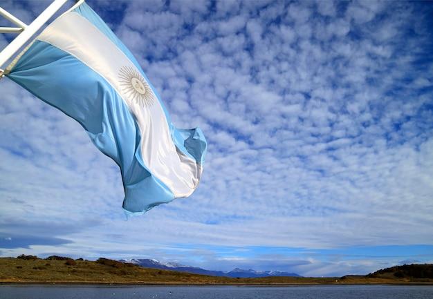 Flagge von argentinien eines kreuzschiffs, das im sonnenlicht gegen hellen bewölkten himmel wellenartig bewegt
