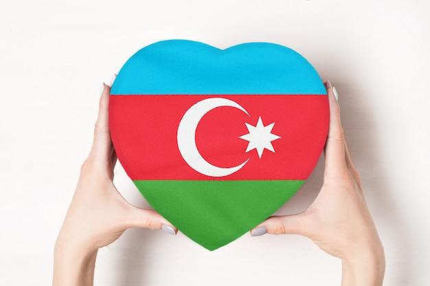 Flagge von aserbaidschan auf einem herzen formte kasten in weibliche hände