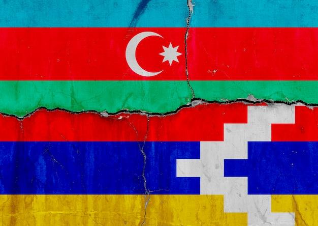 Flagge von aserbaidschan und flagge der republik berg-karabach (artsakh) auf gebrochener mauer