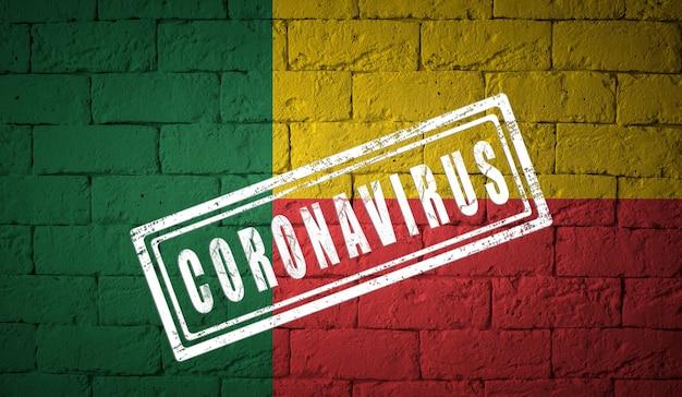 Flagge von benin auf backsteinmauertextur, die vom coronavirus corona-viruskonzept gestempelt ist