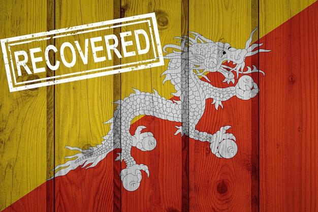 Flagge von bhutan, die die infektionen der coronavirus-epidemie oder des coronavirus überlebt oder sich davon erholt hat. grunge-flagge mit stempel wiederhergestellt