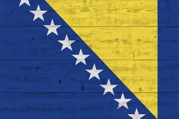 Flagge von bosnien und herzegowina auf altem holzbrett gemalt