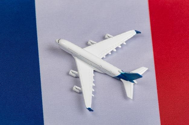 Flagge von frankreich und spielzeugflugzeug. konzept des flugverkehrs in frankreich. flugreisen in europa nach quarantäne
