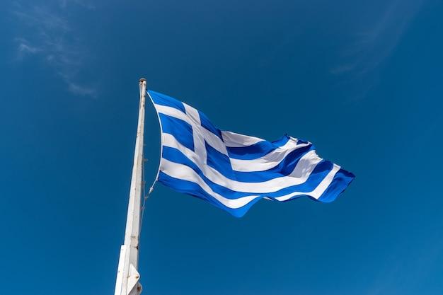 Flagge von griechenland auf fahnenmast gegen den blauen himmel