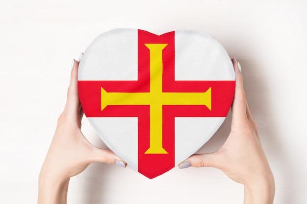 Flagge von guernsey auf einem herzen formte kasten in weibliche hände.