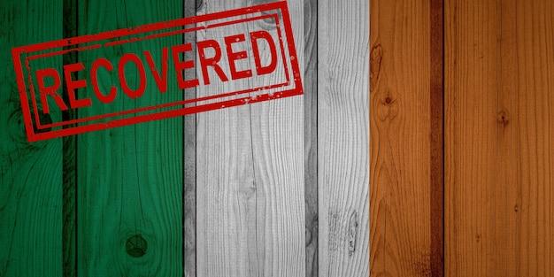 Flagge von irland, die die infektionen der corona-virus-epidemie oder des coronavirus überlebt oder sich davon erholt hat. grunge-flagge mit stempel wiederhergestellt