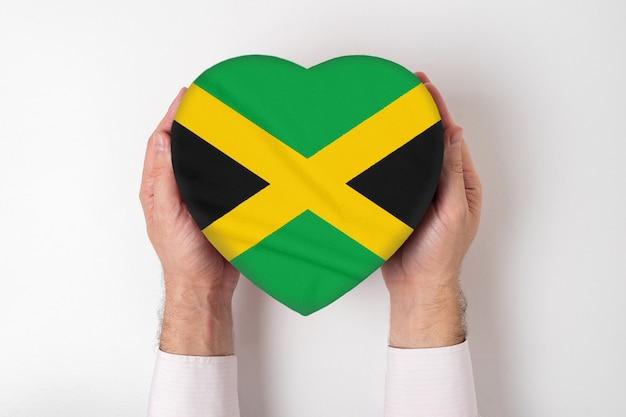 Flagge von jamaika auf einer herzförmigen schachtel in den männlichen händen. weißer hintergrund