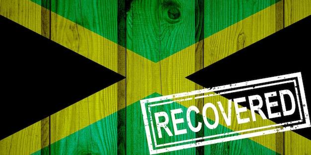 Flagge von jamaika, die die infektionen der corona-virus-epidemie oder des coronavirus überlebt oder sich erholt hat. grunge-flagge mit stempel wiederhergestellt