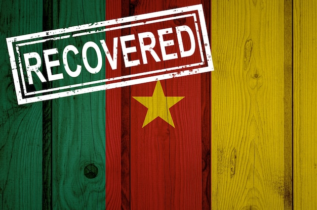 Flagge von kamerun, die die infektionen der corona-virus-epidemie oder des coronavirus überlebt oder sich davon erholt hat. grunge-flagge mit stempel wiederhergestellt
