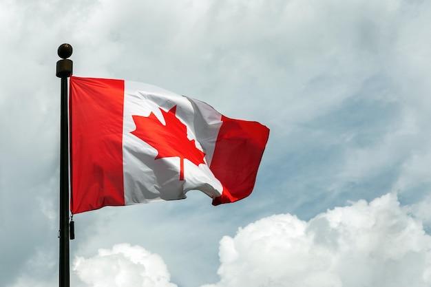 Flagge von kanada auf fahnenmast, der im himmel schwimmt