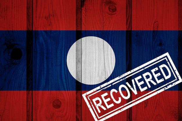 Flagge von laos, die die infektionen der corona-virus-epidemie oder des coronavirus überlebt oder sich davon erholt hat. grunge-flagge mit stempel wiederhergestellt