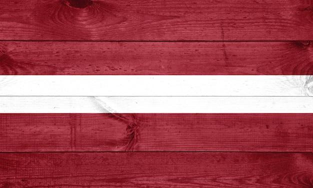 Flagge von lettland auf hölzernem hintergrund, oberfläche. holzwand, bretter. nationalflagge.