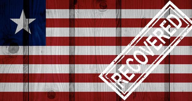 Flagge von liberia, die die infektionen der corona-virus-epidemie oder des coronavirus überlebt oder sich davon erholt hat. grunge-flagge mit stempel wiederhergestellt