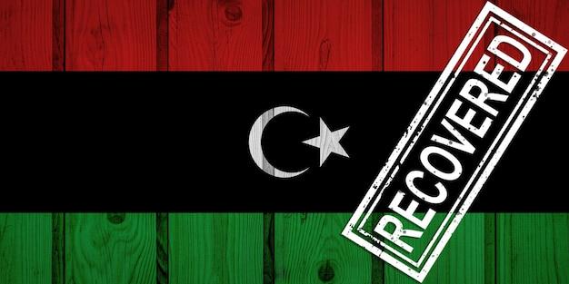 Flagge von libyen, die die infektionen der corona-virus-epidemie oder des coronavirus überlebt oder sich erholt hat. grunge-flagge mit stempel wiederhergestellt