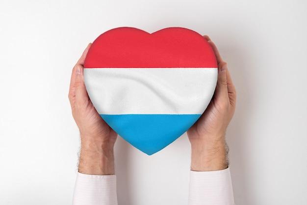 Flagge von luxemburg auf einer herzförmigen schachtel in den männlichen händen