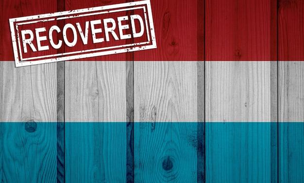 Flagge von luxemburg, die die infektionen der coronavirus-epidemie oder des coronavirus überlebt oder sich davon erholt hat. grunge-flagge mit stempel wiederhergestellt