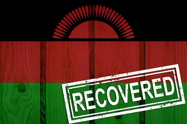 Flagge von malawi, die die infektionen der corona-virus-epidemie oder des coronavirus überlebt oder sich davon erholt hat. grunge-flagge mit stempel wiederhergestellt