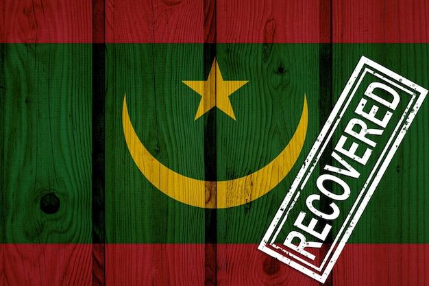 Flagge von mauretanien, die die infektionen der corona-virus-epidemie oder des coronavirus überlebt oder sich davon erholt hat. grunge-flagge mit stempel wiederhergestellt