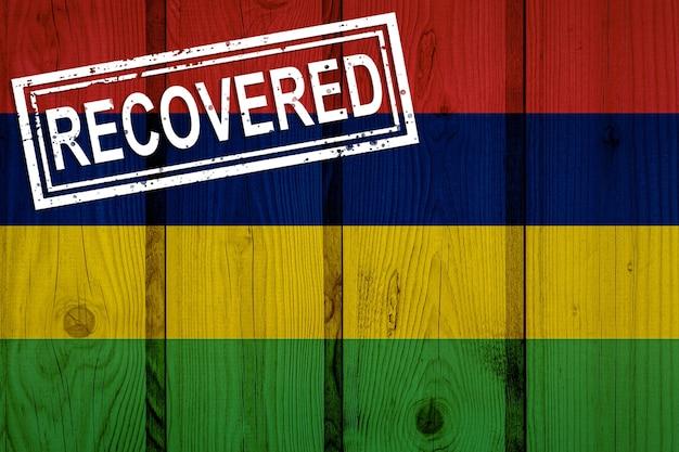Flagge von mauritius, die die infektionen der corona-virus-epidemie oder des coronavirus überlebt oder sich erholt hat. grunge-flagge mit stempel wiederhergestellt