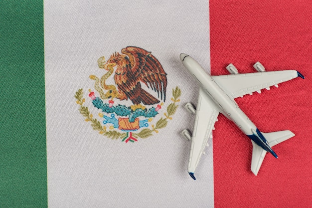Flagge von mexiko und modellflugzeug. wiederaufnahme der flüge nach quarantäne. reise nach mexiko