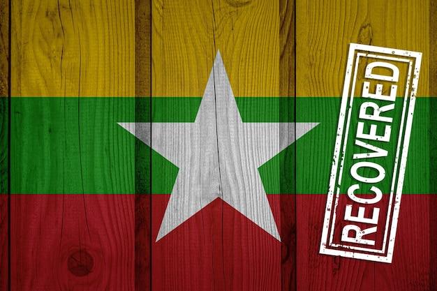 Flagge von myanmar, die die infektionen der corona-virus-epidemie oder des coronavirus überlebt oder sich davon erholt hat. grunge-flagge mit stempel wiederhergestellt