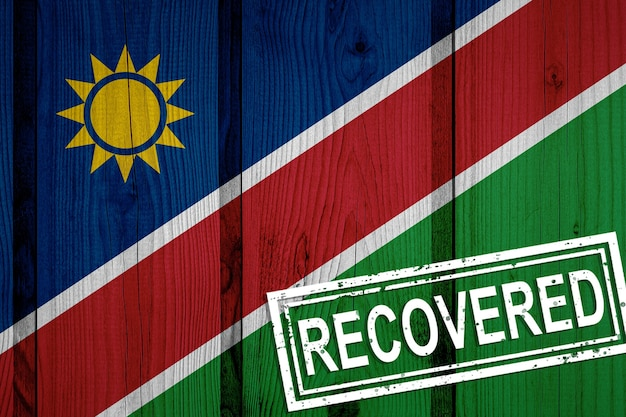 Flagge von namibia, die die infektionen der corona-virus-epidemie oder des coronavirus überlebt oder sich erholt hat. grunge-flagge mit stempel wiederhergestellt