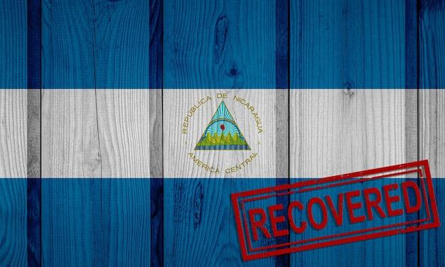 Flagge von nicaragua, die die infektionen der corona-virus-epidemie oder des coronavirus überlebt oder sich davon erholt hat. grunge-flagge mit stempel wiederhergestellt