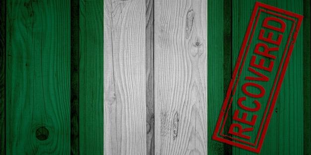 Flagge von nigeria, die die infektionen der corona-virus-epidemie oder des coronavirus überlebt oder sich erholt hat. grunge-flagge mit stempel wiederhergestellt