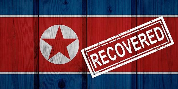 Flagge von nordkorea, die die infektionen der coronavirus-epidemie oder des coronavirus überlebt oder sich davon erholt hat. grunge-flagge mit stempel wiederhergestellt