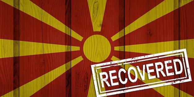 Flagge von nordmazedonien, die die infektionen der coronavirus-epidemie oder des coronavirus überlebt oder sich davon erholt hat. grunge-flagge mit stempel wiederhergestellt
