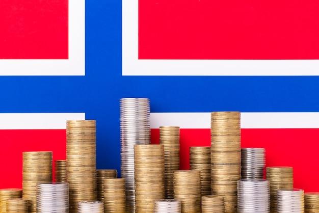 Flagge von norwegen mit hohen stapel von münzen im vordergrund