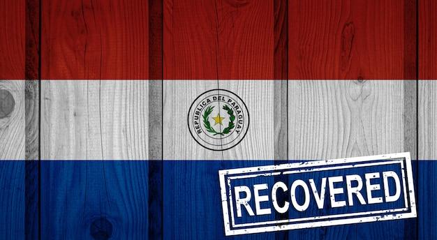 Flagge von paraguay, die die infektionen der corona-virus-epidemie oder des coronavirus überlebt oder sich davon erholt hat. grunge-flagge mit stempel wiederhergestellt