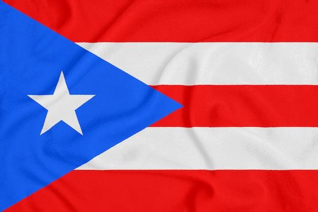 Flagge von puerto rico auf strukturiertem stoff. patriotisches symbol