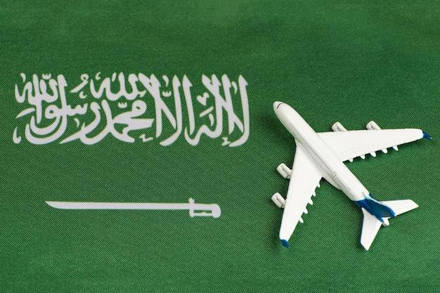 Flagge von saudi-arabien und modellflugzeug. grenzen nach quarantäne öffnen. reisen