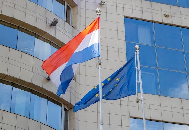 Flaggen der niederlande und der europäischen union am fahnenmast
