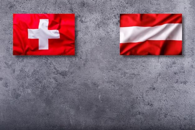 Flaggen der schweiz und österreichs auf konkretem hintergrund.
