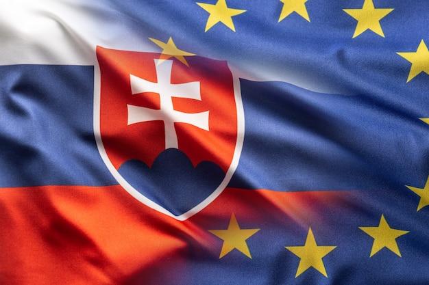 Flaggen der slowakischen republik und der eu wehen im wind.